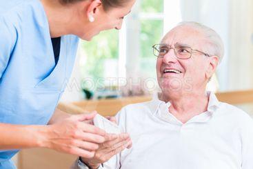 Nurse giving senior man prescription drugs