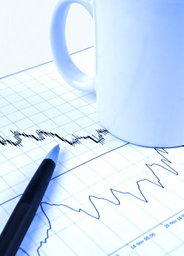 Pen and cup on stock chart