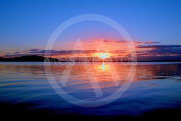 Tranquil orange lake sunrise seascape with...