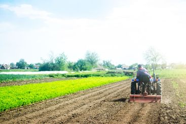 A farmer on a tractor cultivates a field before a new...
