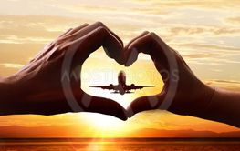 Hands of lovers and taking-off plane