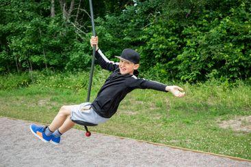 Pojke som åker linbana på lekplats utomhus i park.