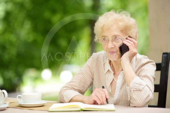 Beautiful senior lady with curly white hair working in...