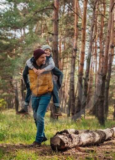 father piggybacking son in forest