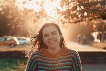 Young woman smiling during a colorful sunset in a...