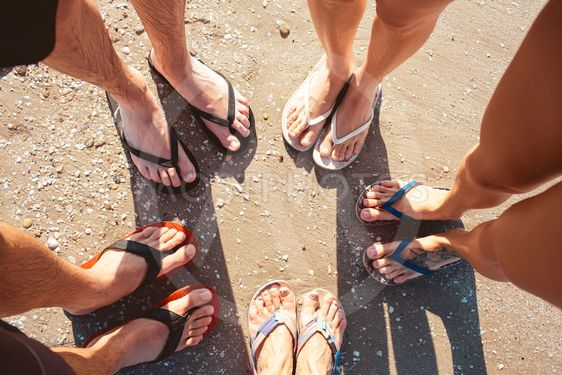 Five pare of legs on the sand of the beach