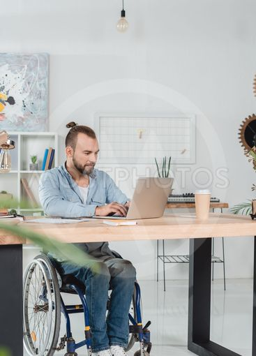 man on wheelchair working with laptop