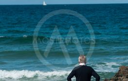 old man standing in front of wild coast in...