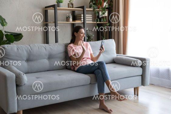 Smiling Arabian woman holding smartphone, waving hand,...