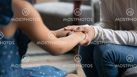 Close up caring mother holding little daughter hands,...