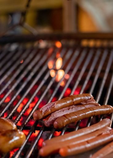 Appetizing delicious sausages lie on the grill of a...