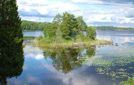 Sjö med liten ö som tillsammans med moln speglar sig i...