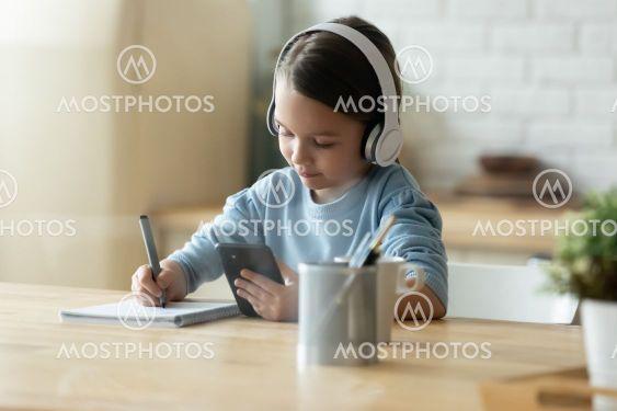 Focused little european kid using smartphone for study.