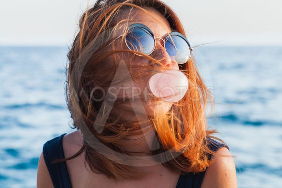 Young woman blowing bubble gum by the sea