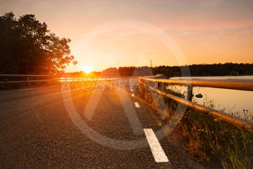 Road and bridge with white border signs during a sunset,...