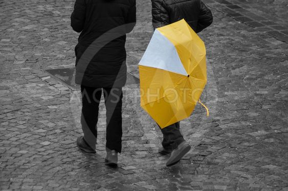 men with yellow umbrella on cobbles place in the city