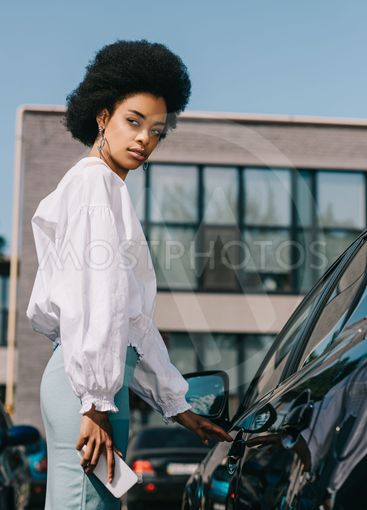 attractive african american businesswoman opening car on...