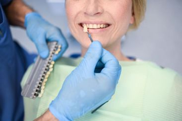 Dentist checks the level of patient's teeth whitening...