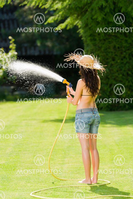 Sommeren haven kvinde play med vand slange