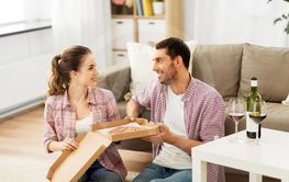 couple with wine eating takeaway pizza at home