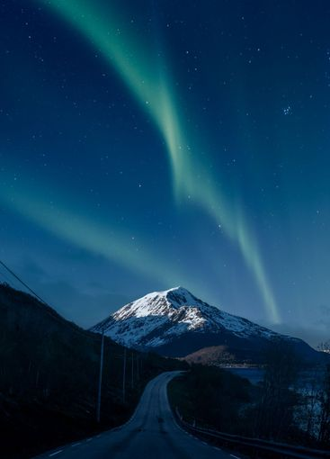 Northern lights over a mountain and road in Norway