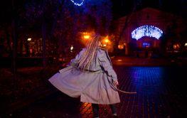 Girl with dreadlocks walking at night street of city...