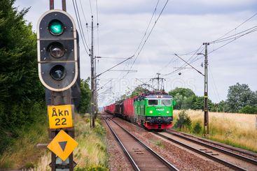 Dubbelspårig järnväg med ett godståg på ena spåret och en...