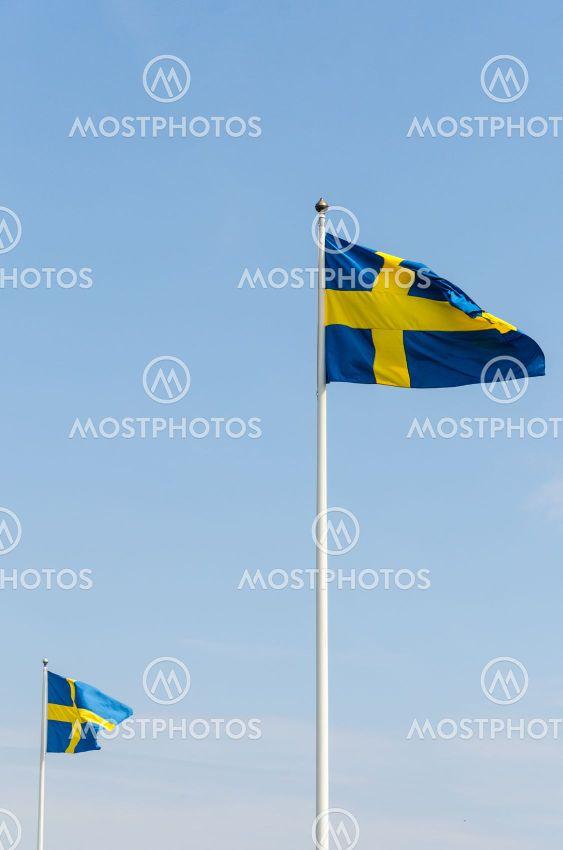 Svenska flaggor vajar på  flaggstänger