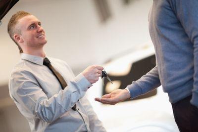 Smiling man giving keys to a man