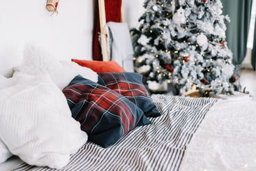 Bedroom interior with large bed and christmas tree with...