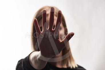 selective focus of victim of bullying showing stop sign...