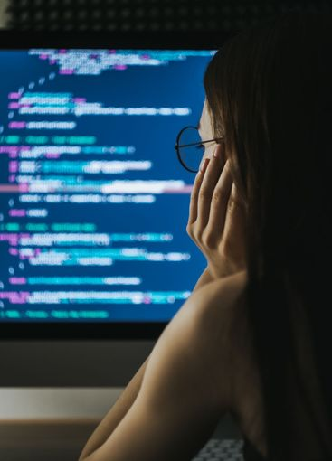 Young female programmer writes program code on a...