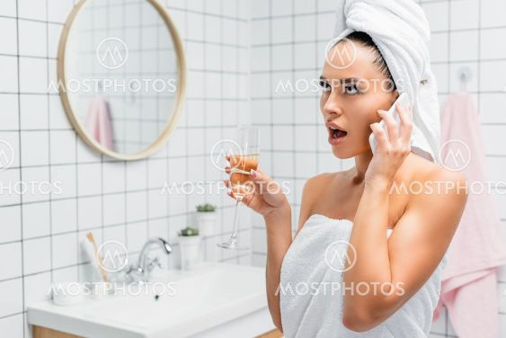 Shocked woman in towels talking on smartphone while...