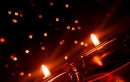 Två brinnande stearinljus i mörkret- Silvertid
