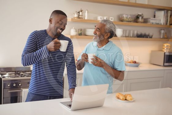 Father and son using laptop while having coffee in kitchen