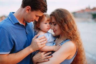 mother and father gently hold their daughter in their arms