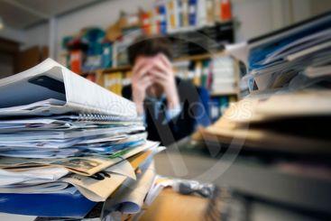 Frustrated man sitting desperate over paper work at desk