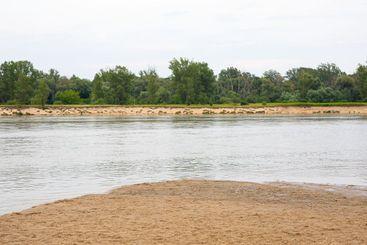 A calm river, beach and green trees
