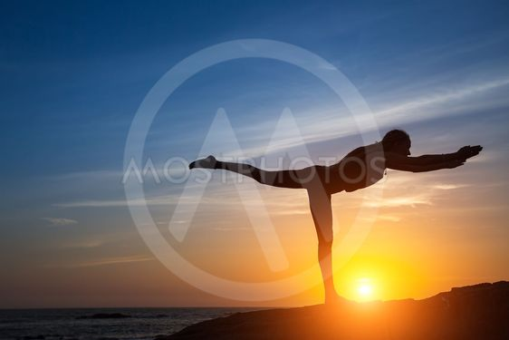 Silhouette of woman doing fitness exercise on the sea...