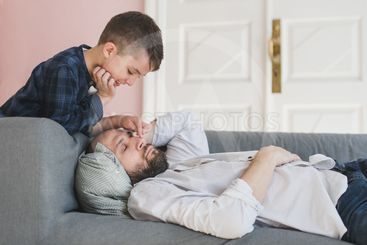 Smiling boy wakes up a father.