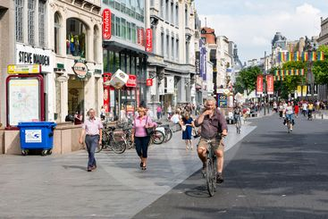 People and cyclists in main shopping street of Antwerp,...