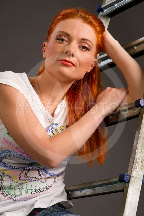 young red-haired girl leaning on a ladder on a gray...