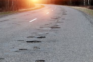 The road in disrepair with a lot of potholes. Cars go...