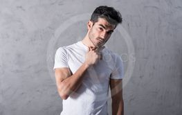 A thinking young man in a white tshirt