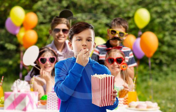 boy eating popcorn at birthday party