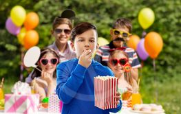 boy eating popcorn at birthday party