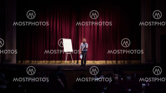 Male caucasian speaker giving presentation in hall at...
