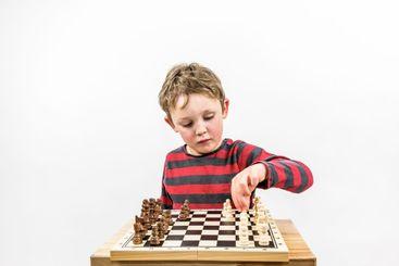 Pojke som spelar schack för sig själv.