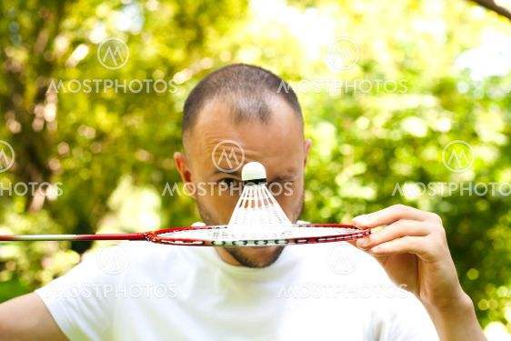 Young man winks and covers her face with a racket...