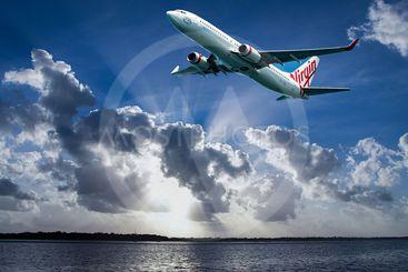 Aircraft in flight with cumulonimbus cloud in blue sky....